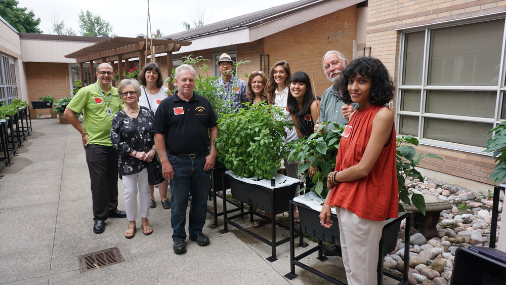 In the front section of the resident garden. From left to right: Travis Durham, Wendy's colleague/neighbour, Wendy Smith, Peter Dickey (Owner, Beekeeper– Dickey Bee Honey), Chris Wong (Partner– The Growing Connection), Sandra Wolf (Manager of Environmental Services– Grove Park Home), Hayley Lapalme, Cheryl Hsu, Robert Patterson (Founder– The Growing Connection), Vidhi Gupta