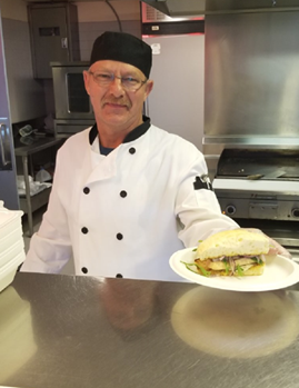 Nutrition and Food Services Cook, Paul Nieman, proudly displays the salmon on bannock sandwich, served in Regina cafeterias in celebration of National Aboriginal Day (Photo from Stephanie Cook)