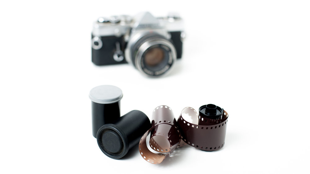Analog photo reels with camera in background