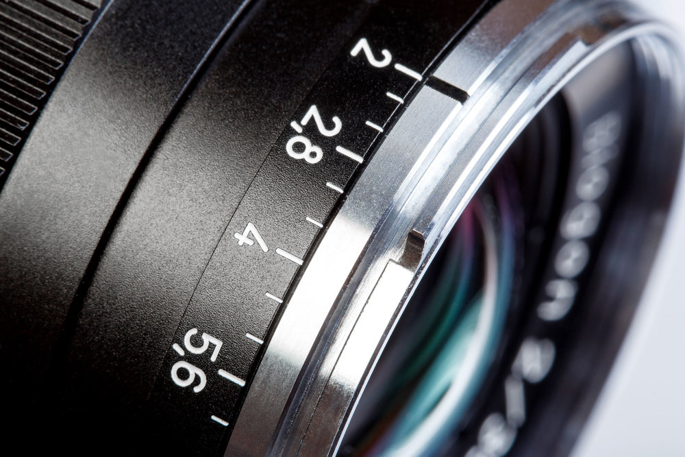 A retro camera lens with a mechanical aperture ring. The f/2 to f/5.6 markings are visible, with the small black line on the silver ring indicating that the aperture is currently set to a value of f/2.