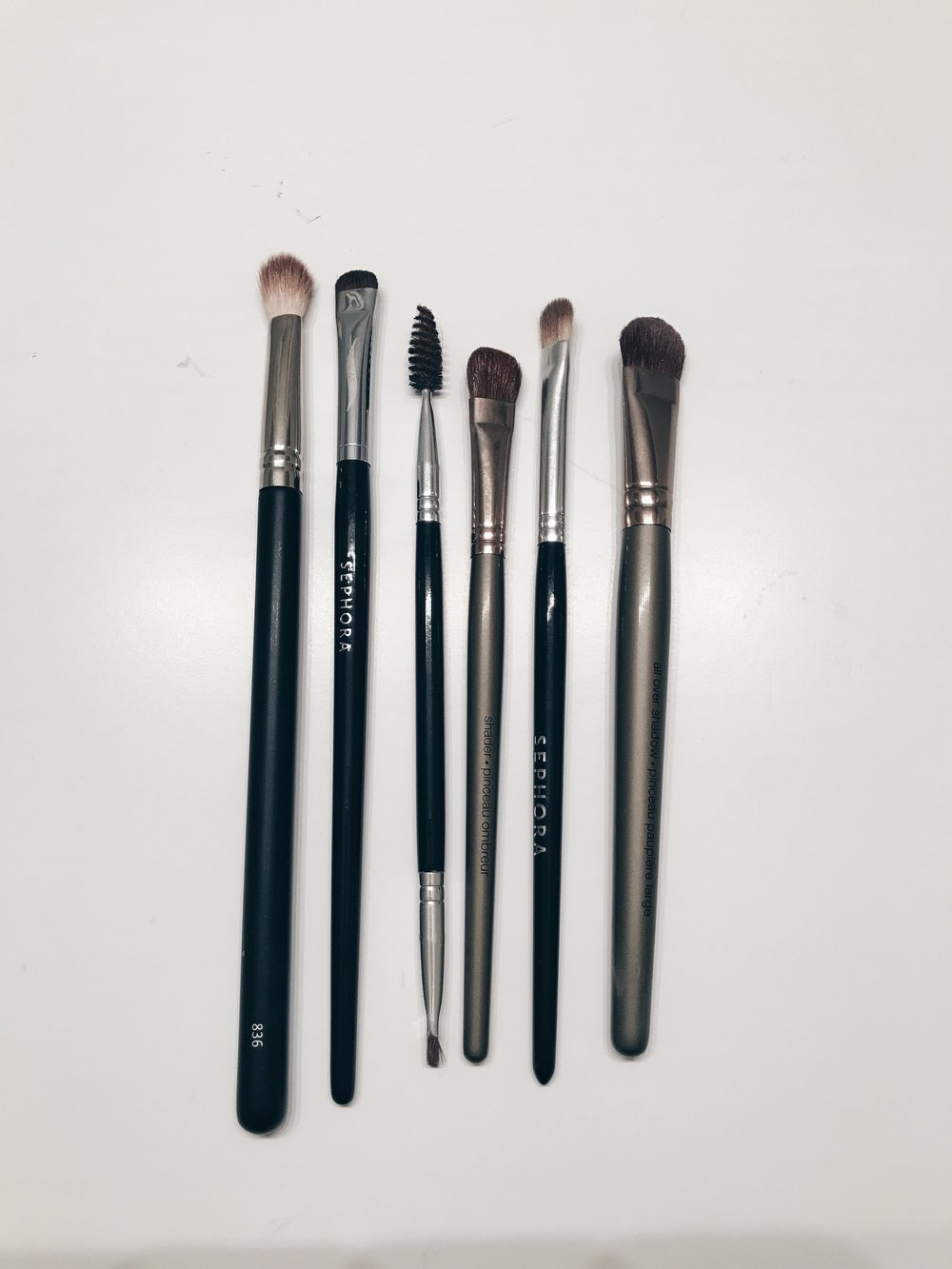 How I use each brush from right to left. Brush 1: Japonesque 836 I use this for the darkest color in my shadow routine. This is used in the corner and blended into the crease.  Brush 2: Smudge Brush I use this brush to smudge a darker color under my lower lash line for that extra smokey effect.  Brush 3: Anastasia Brush #12 This brush is perfect for filling in my brows. I can brush them and use the angle to fill them in beautifully.  Brush 4: Shader Brush Generally, I use this brush second in my routine. I use it to blend a color in my crease and for a color on my lid.  Brush 5: Precision Shadow Brush This brush I use if I want a concentrated color and usually I will wet it with setting spray. I use it for color on my lid only.  Brush 6: All Over Shadow Brush This is normally the first brush I use for all over shadow. I use this for the lightest color to put on my entire lid or just to highlight under my brow.  *I actually have this brush set and love it!