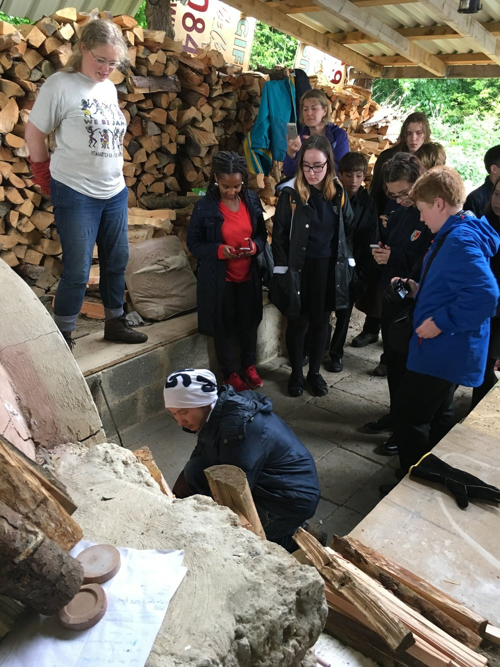 Local school pupils watch Kazuya san stoke the kiln.