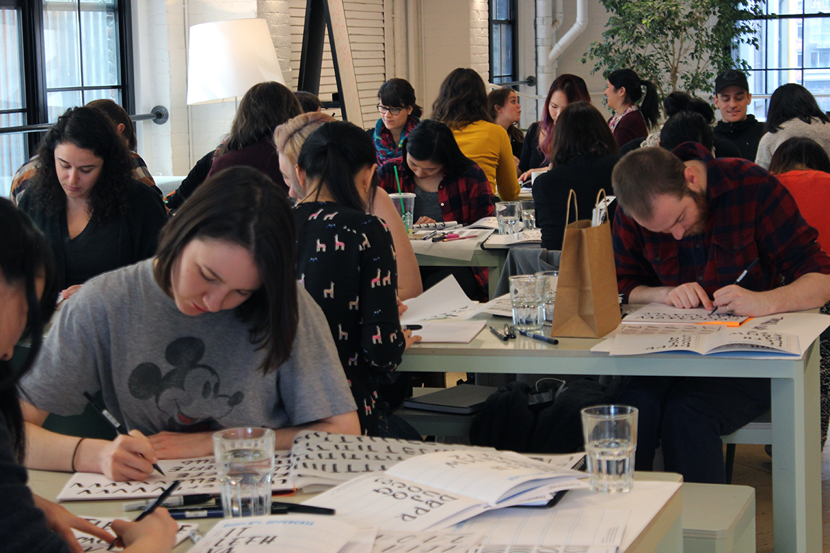Students learning brush lettering in toronto