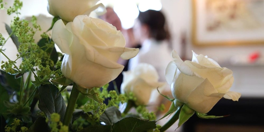 white roses wedding flower arrangement bride in the background | photo credit: Harborview Studios