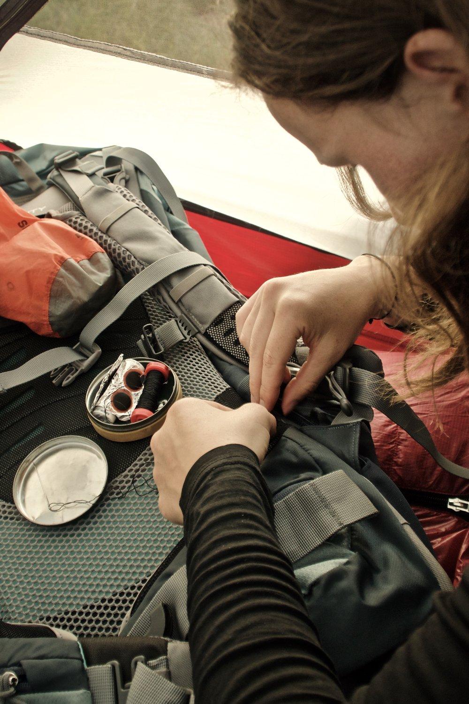 Johanne bruger aftenen på at reparerer noget net i sin nye rygsæk