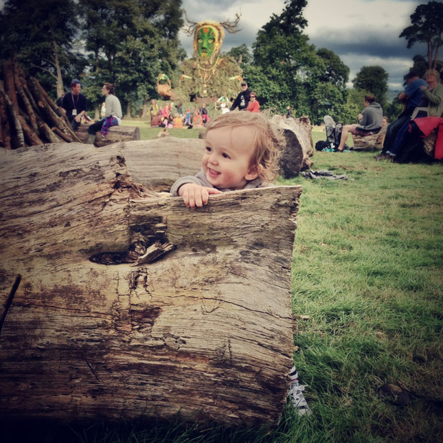baby playing in a field at green man festival
