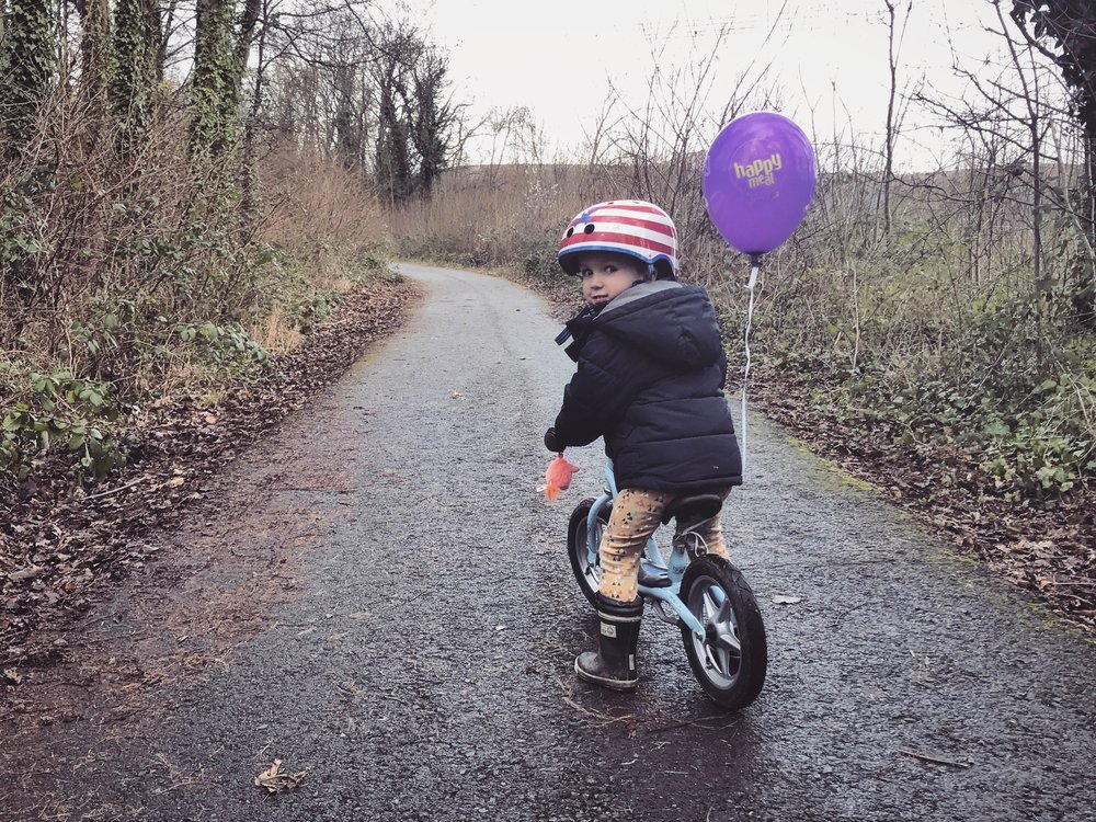 Toddler boy riding his bike with a purple balloon.