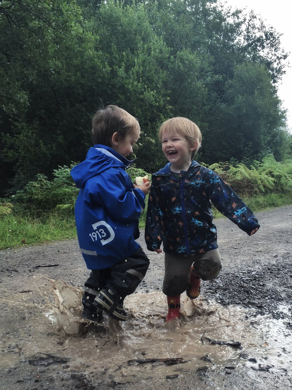 Two little boys splashing in a puddle.