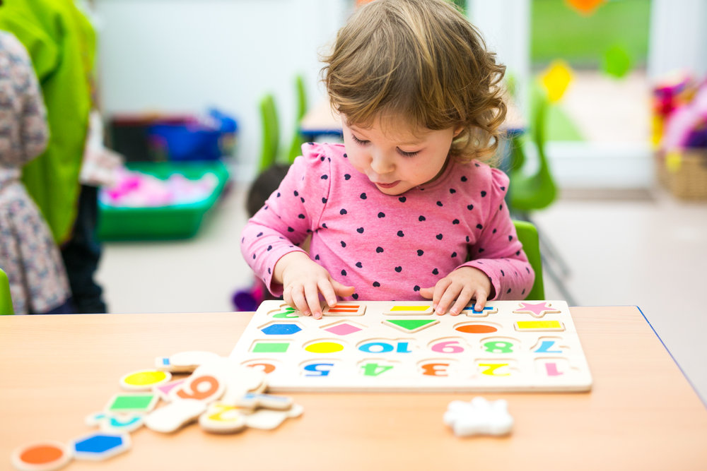 Toddler girl playing with a puzzle at Tiny Tots Nursery Abergavenny