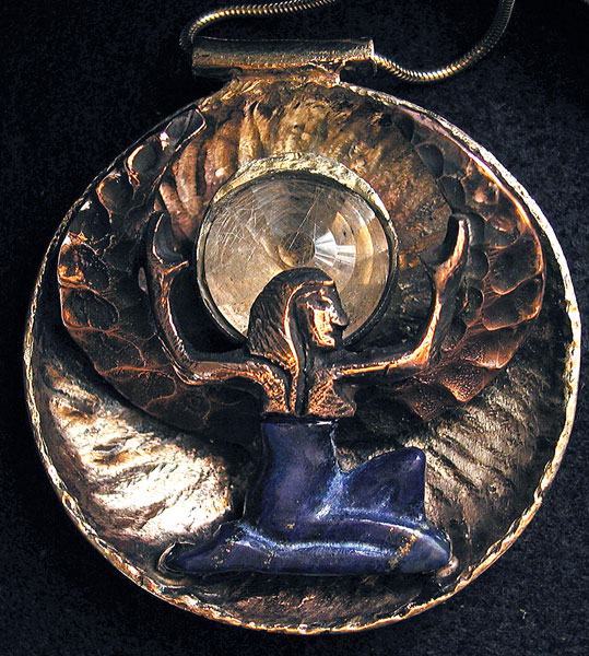 """ISIS"" PENDANT - 2007,  Daniel Macchiarini  4 ounces of red (wings and body), yellow (back) and white (moon setting over Isis head), inlay of Lapis body with rutilated quartz spiral cut stone.  Commissioned by Carlos Santana."