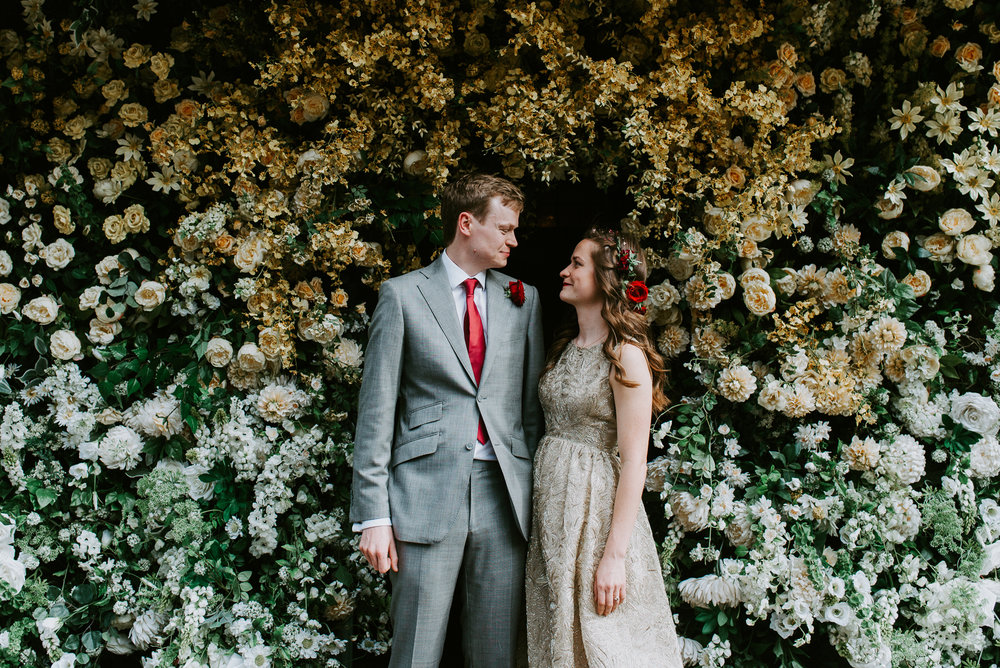 Bride and Groom portrait in front of a spectacular white and yellow flower wall. These two had an intimate wedding celebration in Chelsea, London.