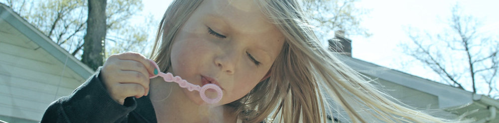 Schmaltz Law Carefree Child Blowing Bubbles Photo