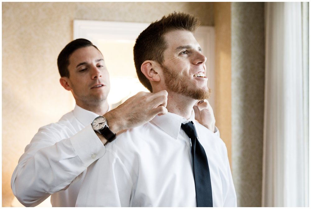 best man adjusting groom's tie