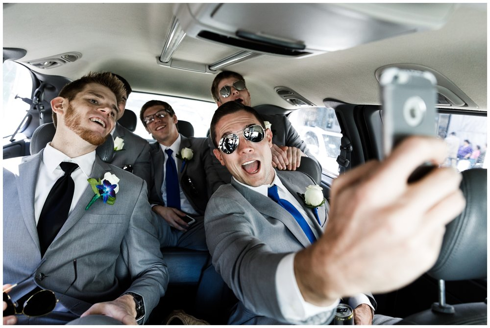 groomsmen and groom taking a selfie in a car