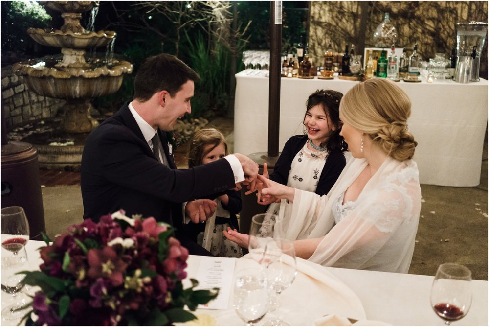 bride and groom talking to flower girls during dinner