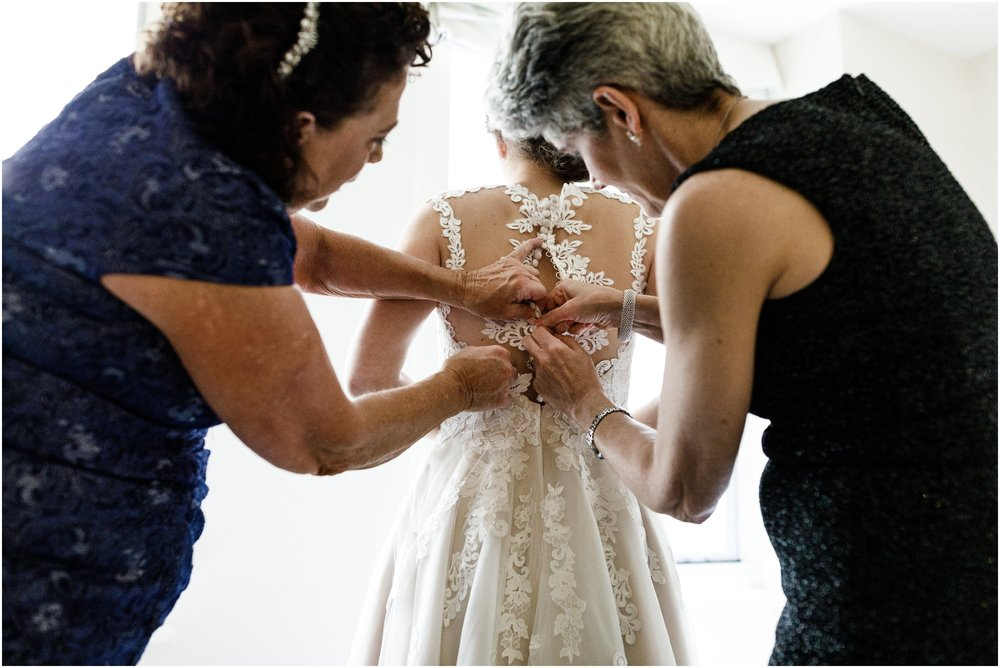 mother of bride helping bride put on her wedding dress