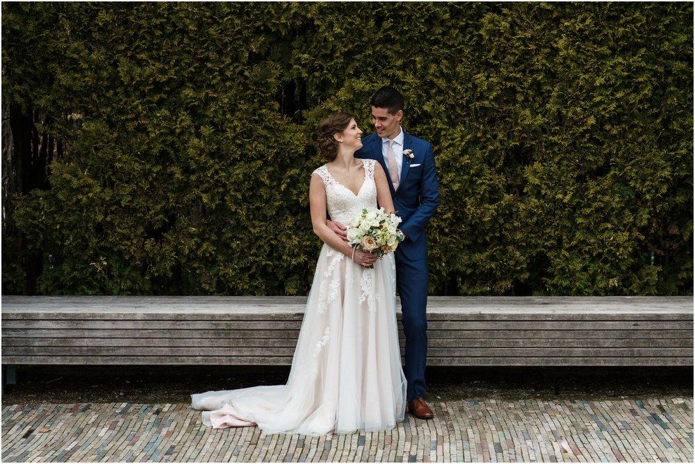 bride and groom posing in Millennium park's Lurie garden
