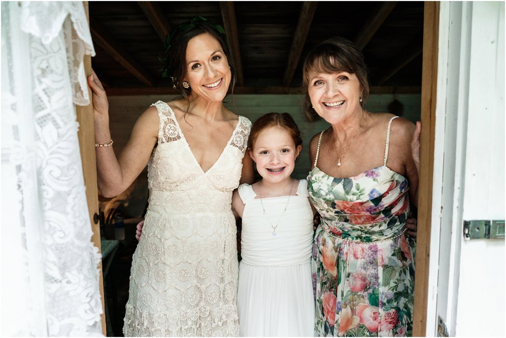 bride posing with her mother and daughter in bridal studio
