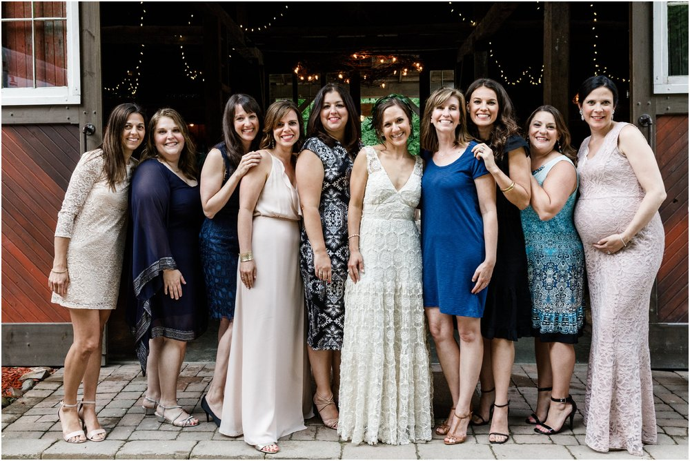 bride and friends posing in front of barn