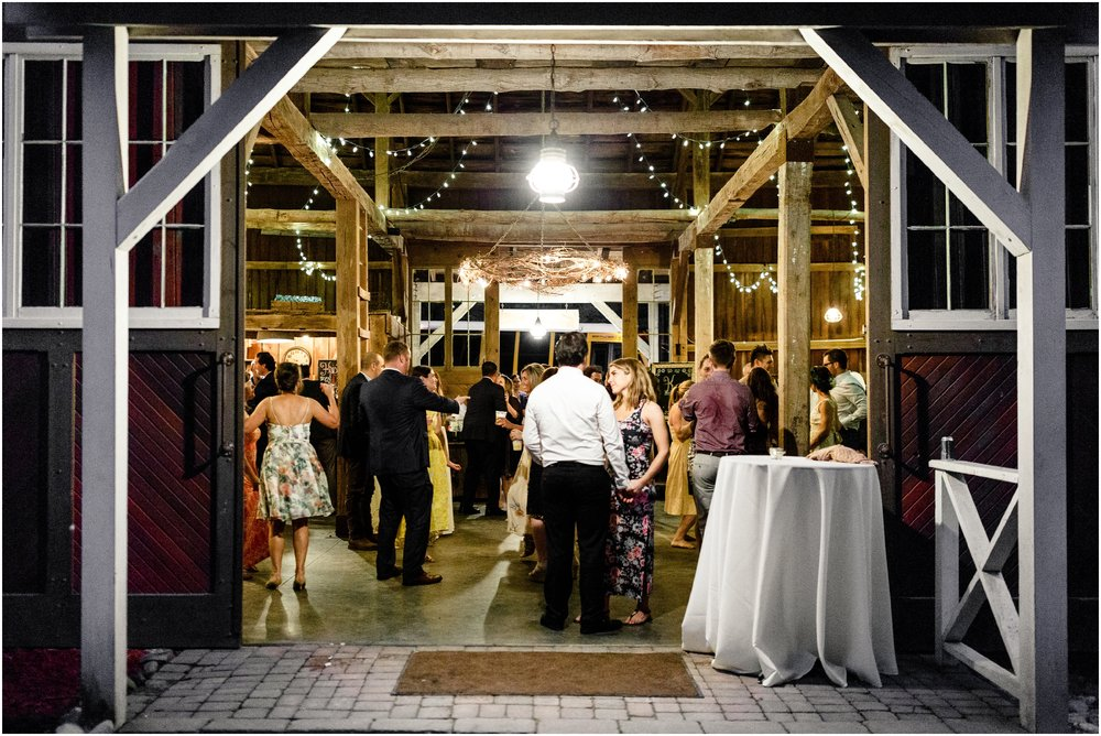 wedding guests dancing during reception in a barn