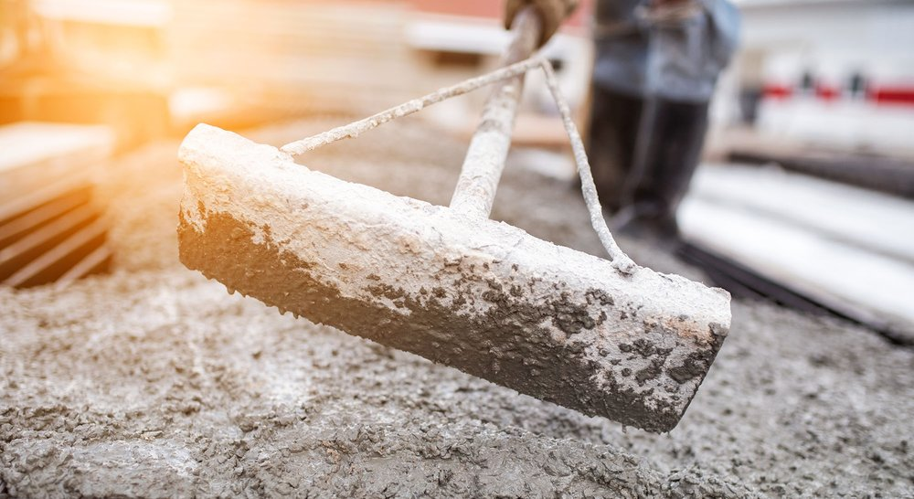 stock-photo-leveling-concrete-with-trowels-laborer-spreading-poured-concrete-selective-focus-a-construction-560978905.jpeg
