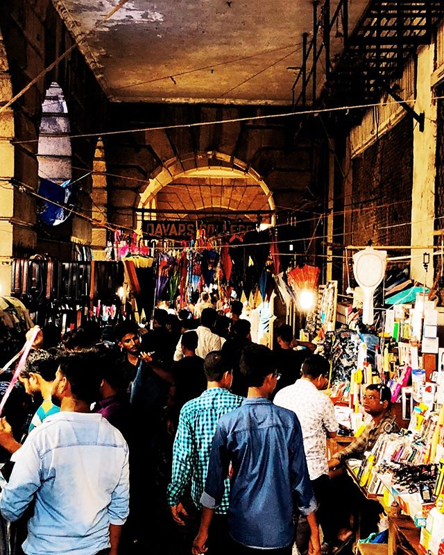 The Markets Of Bombay . Bombay attacks newcomers with a mix of colours, smells, sounds and perpetual movement. Throughout its history it has been a city of opportunity and hustle. People come here to become a Bollywood star, work their way up to fabulous wealth or just have fun and enjoy the atmosphere.  Naturally, shopping is a popular pass time among the city dwellers. The Colaba markets draw the crowds with an eclectic offering of quite literally anything in the world: fashion, furniture, books, jewellery and even car parts are available right here next to each other.  After shopping to their heart's content, people head to the ocean's shore to sip a glass of Sula wine and watch the boats enter and leave the port of this ever great merchant outpost. . . #mumbai #bombay #india #colaba #markets #traders #merchants #opportunity #business #2footsteps #discovery