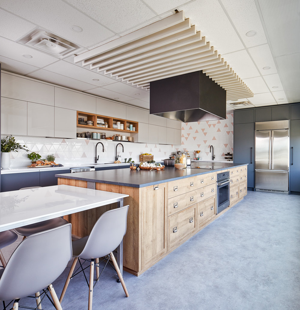 Large hood spans over both cooktops located back to back on the island. Hood vent and the painted wood canopy that surrounds it also creates an interesting focal point and breaks up the institutional feeling of the commercial grid ceiling.
