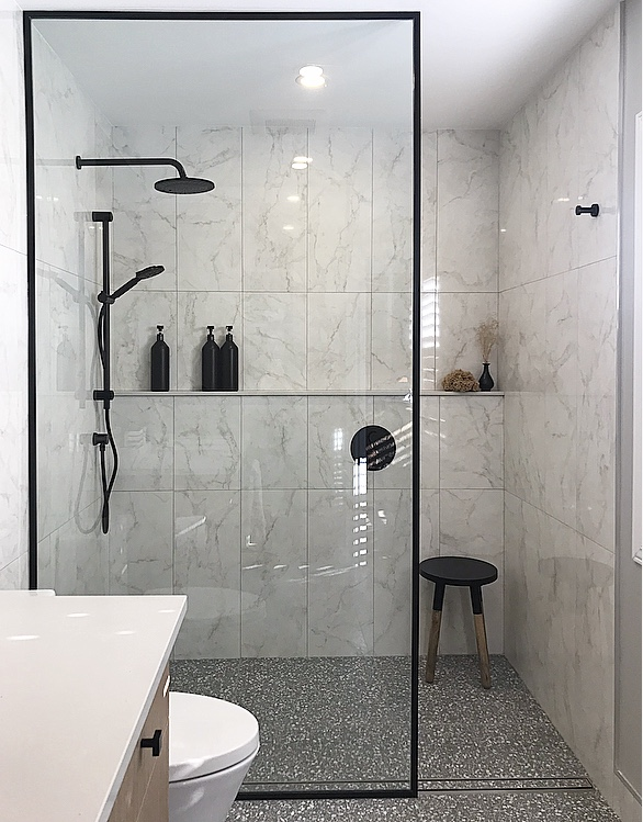 "Shower fixtures: Alt by Aquabrass in Electro Black. Linear drain: Easy Drain. Wall tile: 12"" x 36"" marble-printed porcelain tile, vertical stack installation. Floor tile: Terrazzo-print tile, 24"" x 24"". Toilet: Crosswater. Cabinet hardware: Top Knobs. Robe Hood: Kartners."