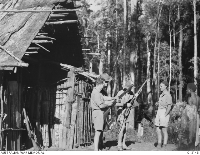 Skindewai, New Guinea. 28 August 1942. A group of Aussies inspect their rifles in camp. From left to right: Stan Tompkinson; Stuey Monroe, New Guinea Volunteer Rifles (NGVR); Private Roy O. Warren and an unidentified member of the NGVR. (Negative by D. Parer). ID P01283.006, Australian War Memorial.
