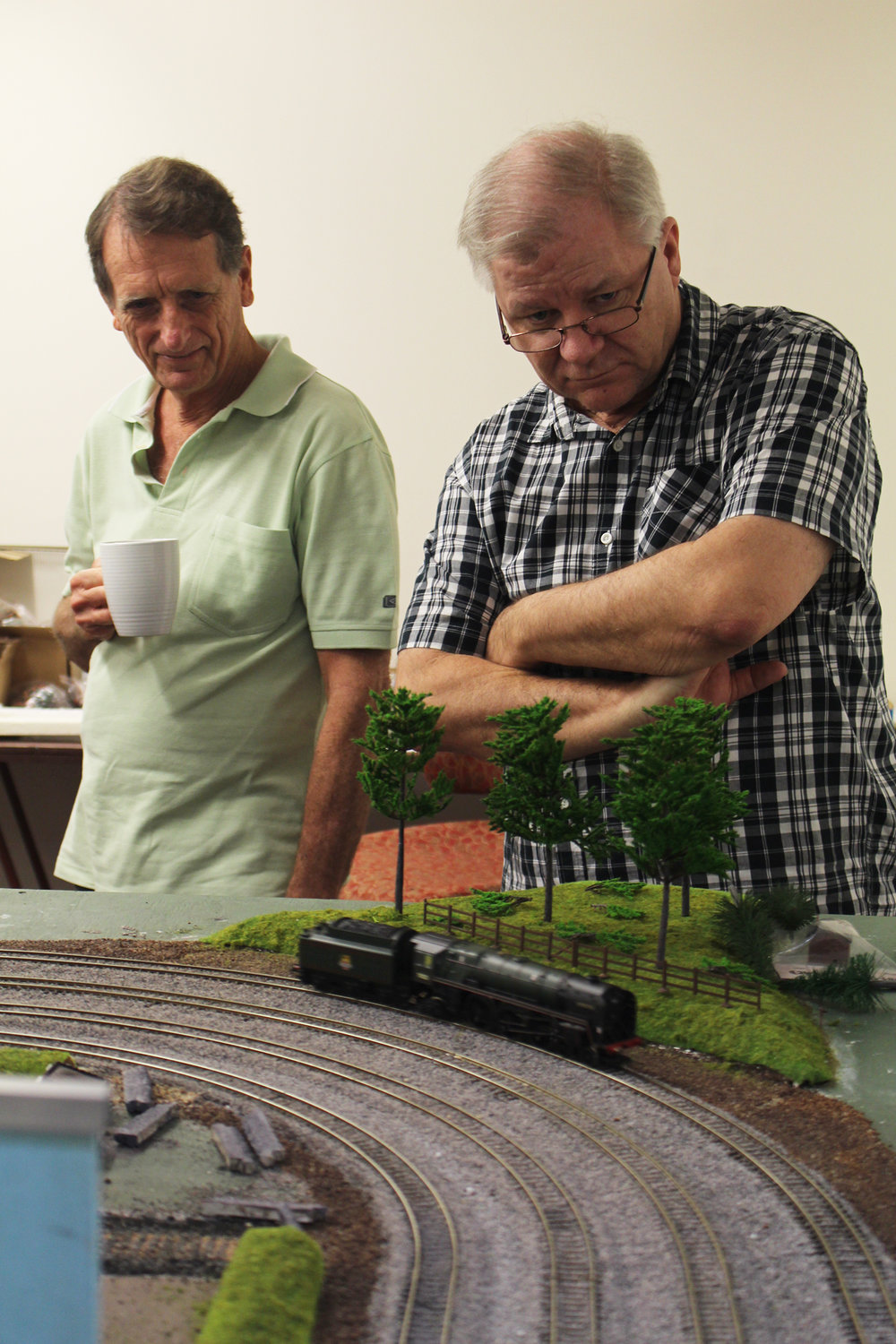 Left to right, visitor Brian McKenzie and founding member Peter Ball watch as the trains move around the track.