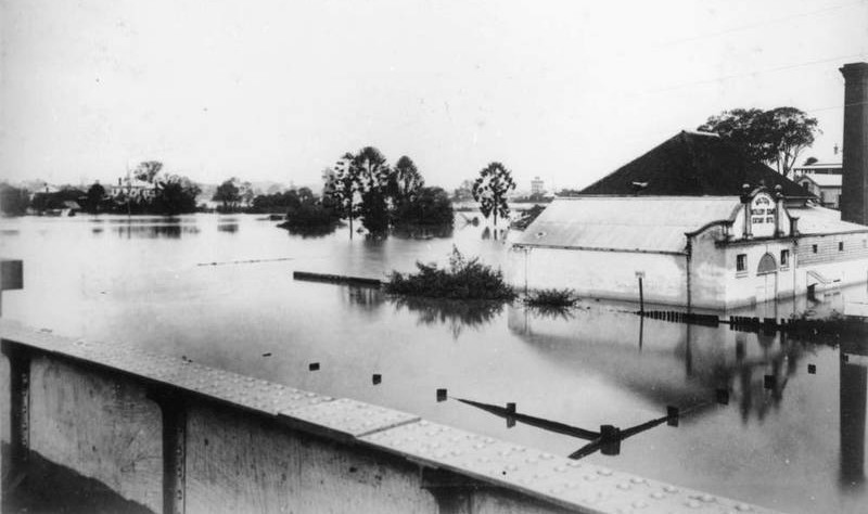 The Milton Distillery in flood in 1890. In the background, the residences of E.J. Bennett and J.G. Cribb are also visible. ( State Library of Queensland )