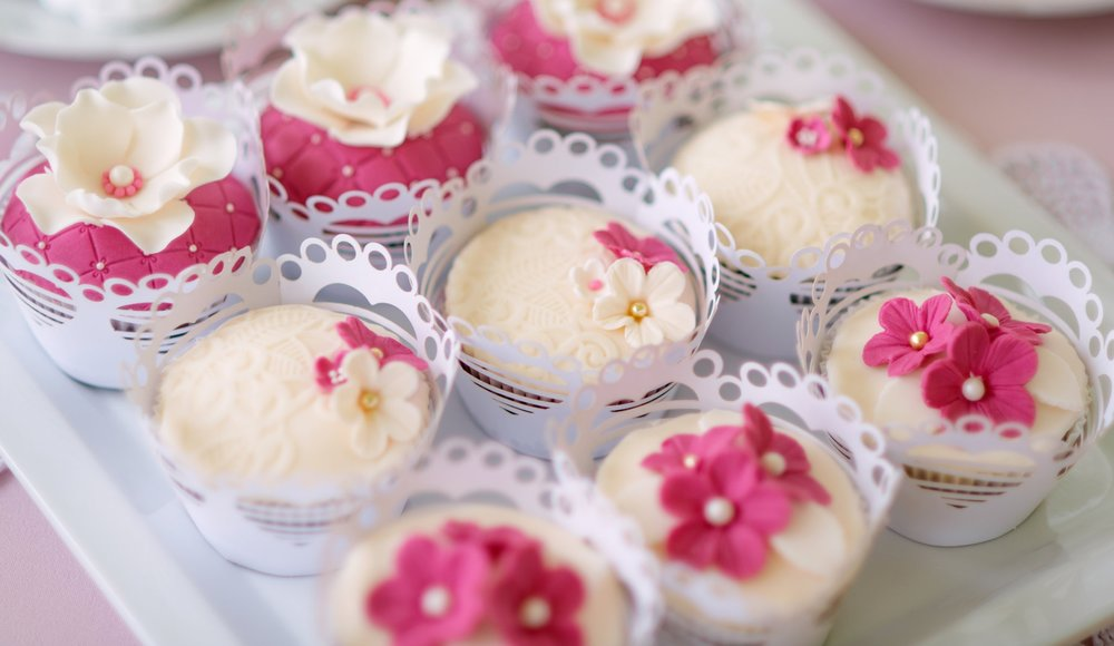 graphicstock-close-up-cupcakes-on-tray-decorated-with-pink-flowers-laid-on-table-with-pink-tablecloth-and-handmade-lace-candy-bar_BdKrEsrfZ.jpg