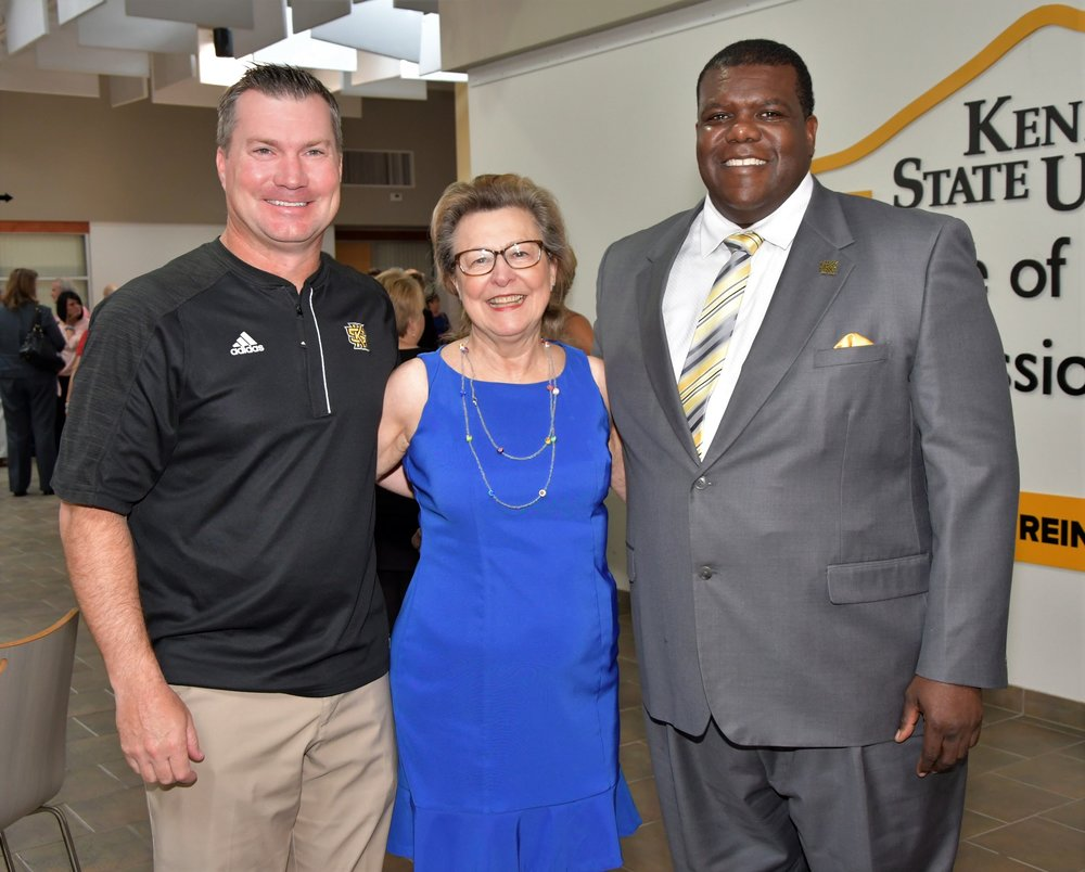 Shelley stands with Milton Overton, KSU Athletics Director, right, at the KBA Tuesday luncheon Aug. 14. Overton was the speaker for the month's event. At left is KSU Head Football Coach Brian Bohannon.