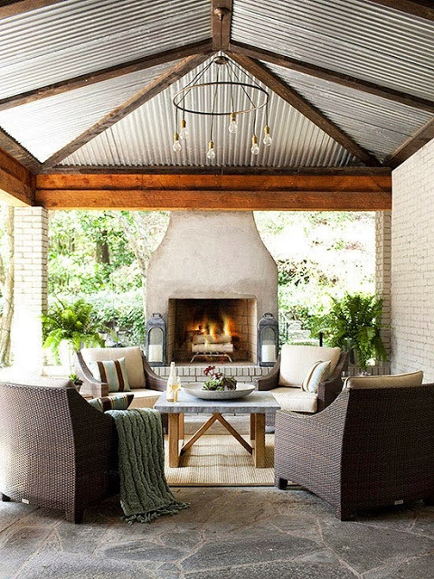 outdoor-living-room-fireplace-steel-roof-flagstone-patio-woven-furniture-cococozy