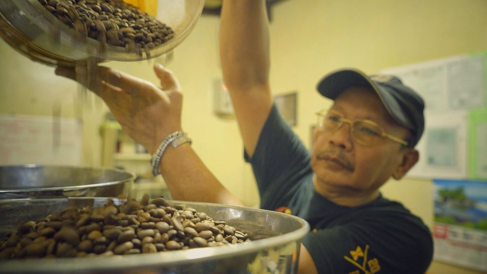 asep pouring beans into roaster.jpeg