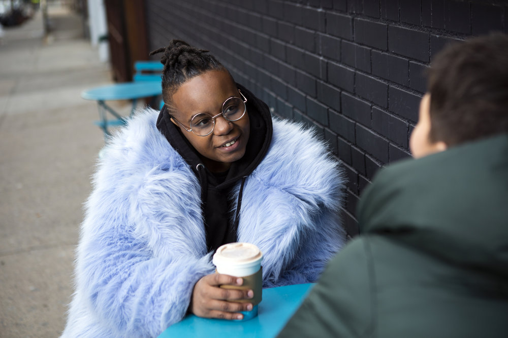 Photo Credit:  The Gender Spectrum Collection . A transmasculine person with a furry blue coat drinking coffee with a friend.
