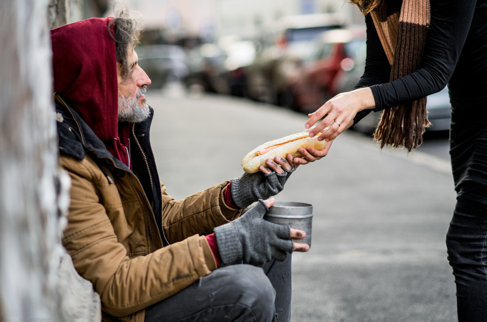 unrecognizable-woman-giving-food-to-homeless-KB3TYVL.jpg