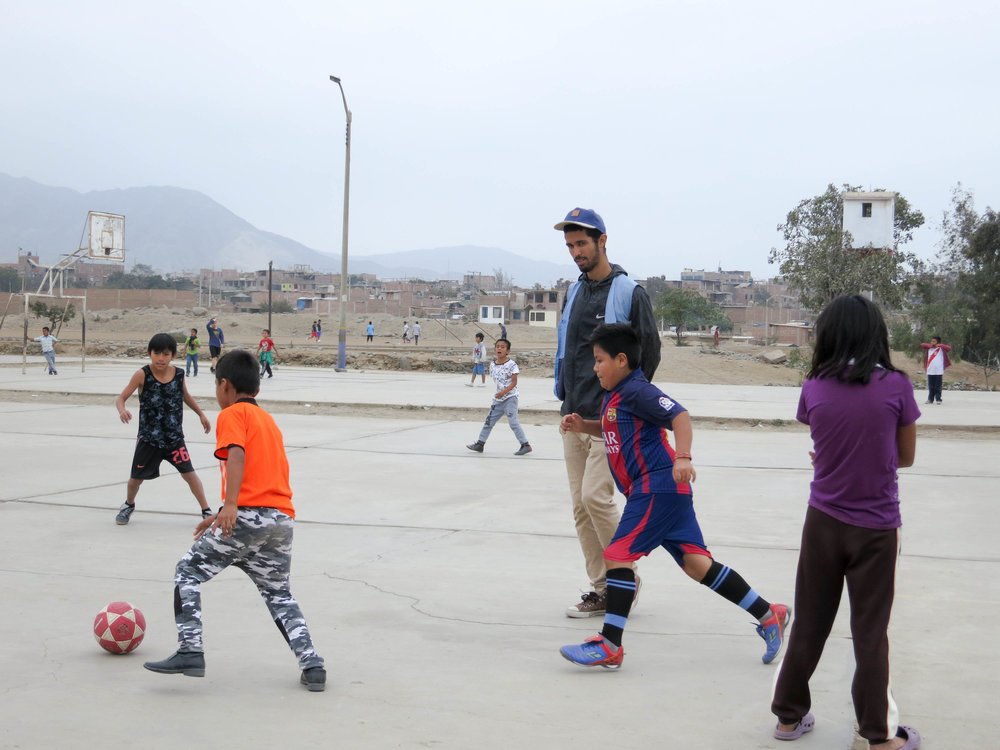 Peruvian kids playing soccer volunteer with SKIP