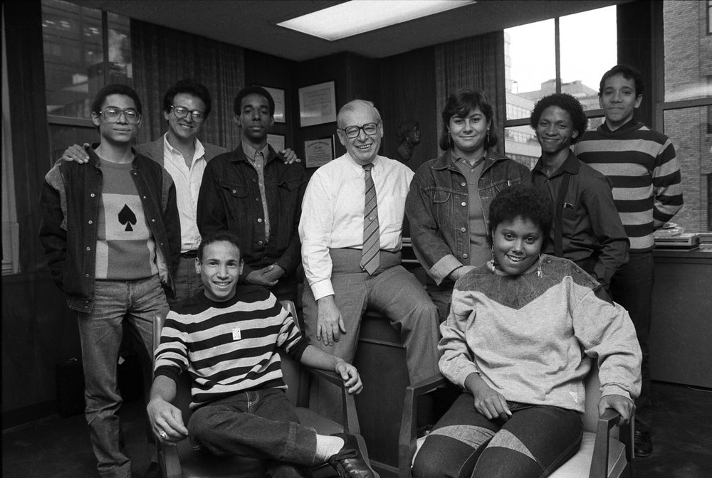 Mr. Lang poses with graduates of his old school, in 1985. (Chester Higgins Jr./New York Times)