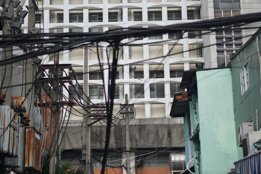 The modernist facade of the An Duong Vuong market behind the tangled electrical work.