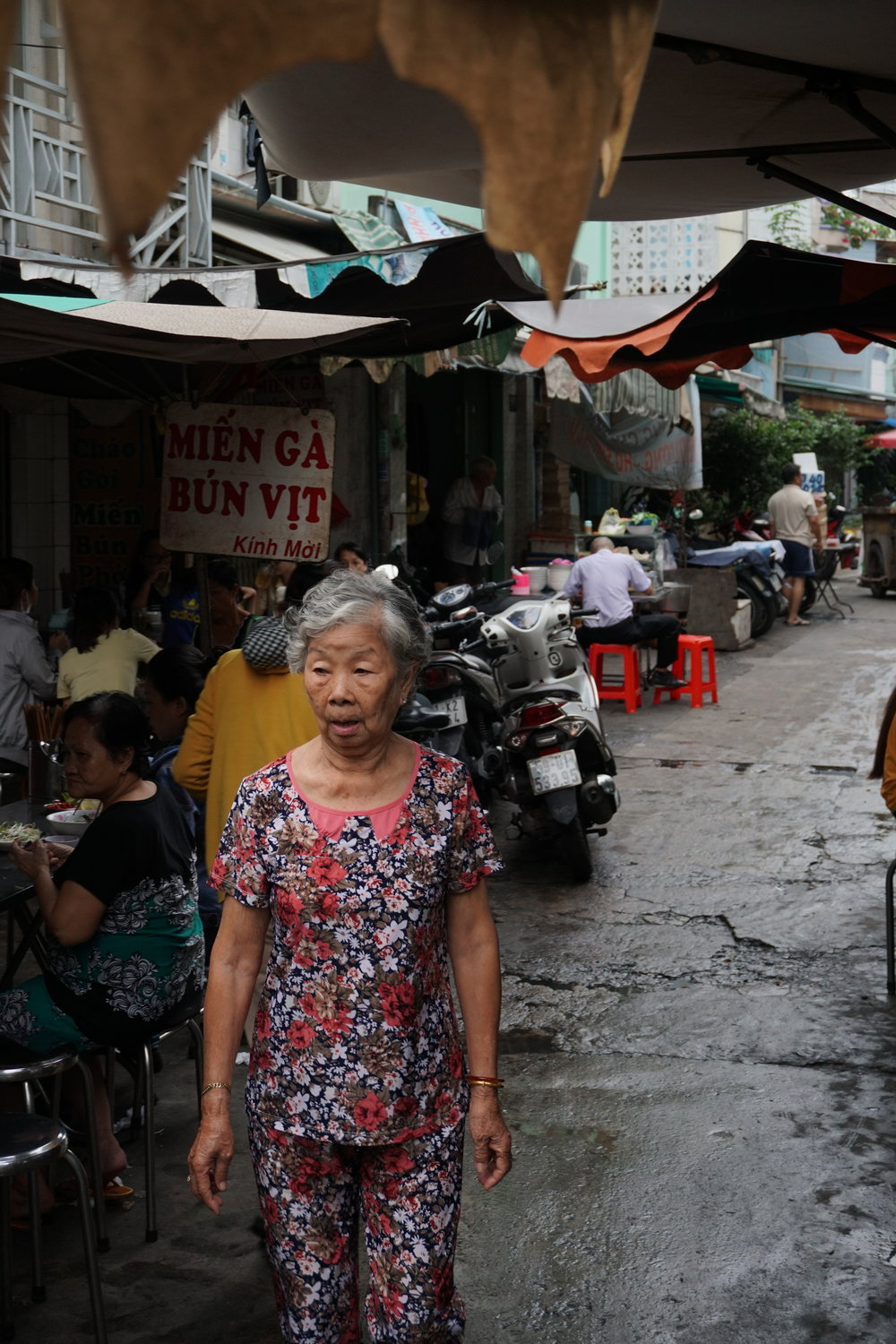 A woman strolls through a narrow alleyway.