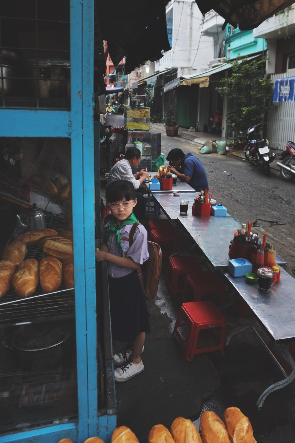 A little girl takes herself to school. But first, banh mi.