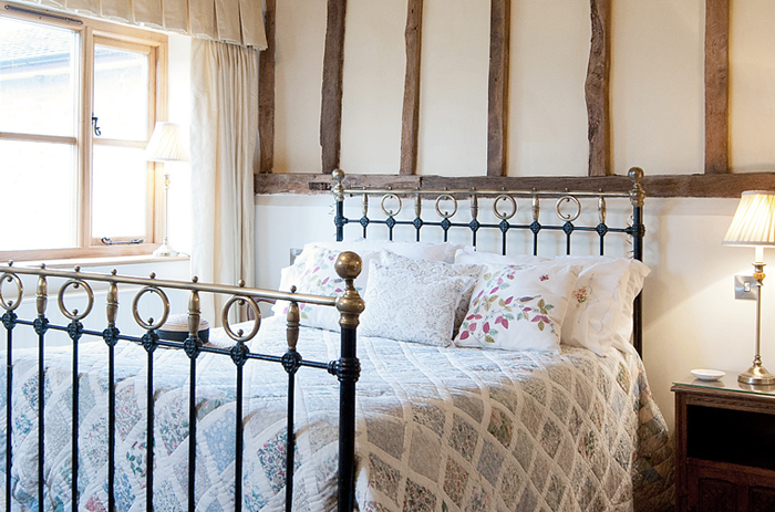 Sourced Victorian bedstead with patchwork quilt