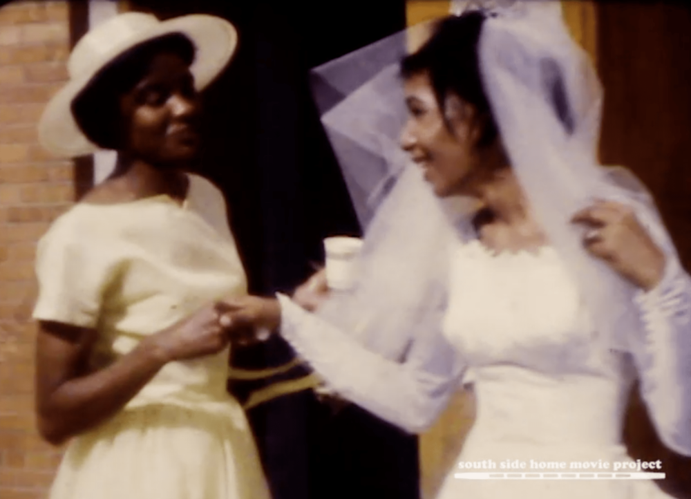 Image: Film still of a dark-skinned Black woman in a light yellow dress smiling and holding the hand of a lighter-skinned Black woman in a white wedding dress with a veil. Film still from the Lynette Frazier Collection, courtesy of the South Side Home Movie Project.