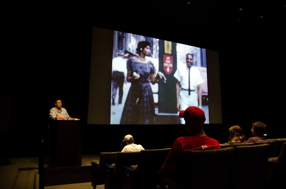 Image: Candace Ming presenting selections from the SSHMP archive at the Logan Center Five Year Bash on October 7, 2017. Candace stands at a podium in front of an audience. Behind her, there is an image of a Black woman and a Black man walking on a street in Chicago. Photo by Martin Awano, Film still from the Lynette Frazier Collection, courtesy of the South Side Home Movie Project