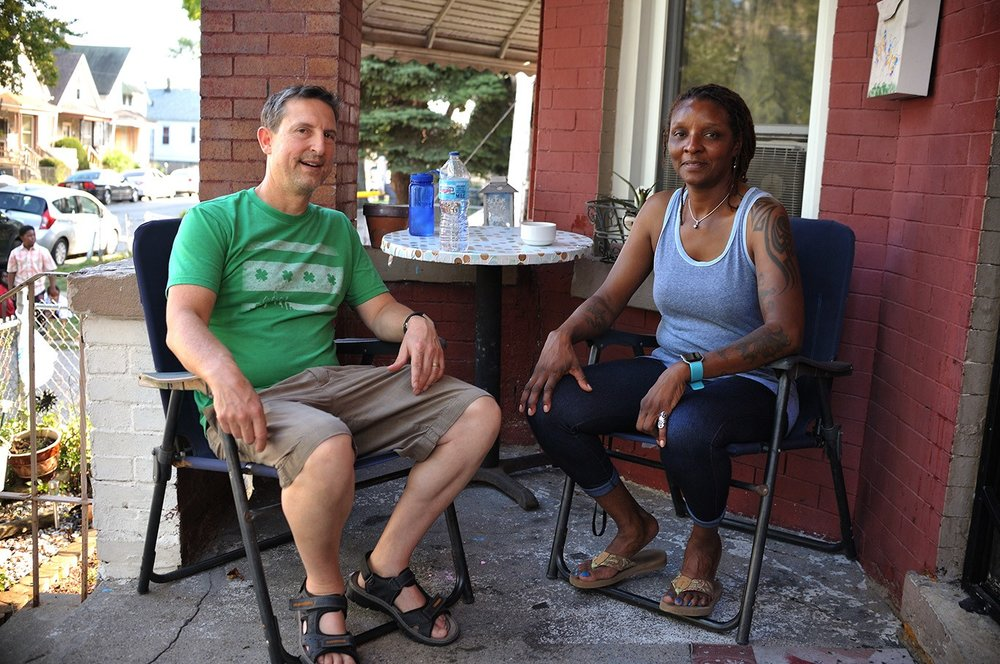Image: Wade (left) and Nanette (right) sit together on Nanette's porch and smile at the camera. Photo courtesy of the artist.