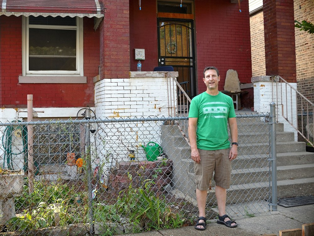 Image: Photograph of Wade on his Map Twin Nanette's front porch in Englewood. He is wearing khaki shorts, a bright green t-shirt with the Chicago flag on the front, and sandals. He looks at the camera with a slight smile on his face. Photo courtesy of the artist.