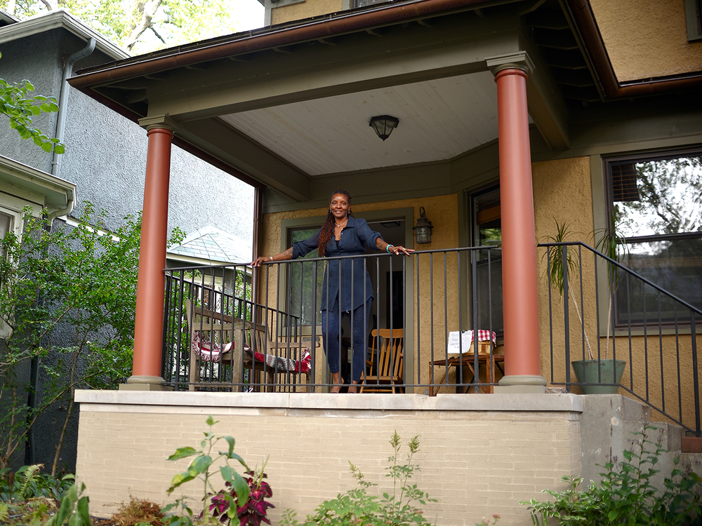 Image: Portrait of Nanette, a Folded Map participant, standing on the front porch of her Map Twin, Wade's house. She is wearing a navy blue shirt with matching leggings. She gazes with a smile at the camera. Photo courtesy of the artist.