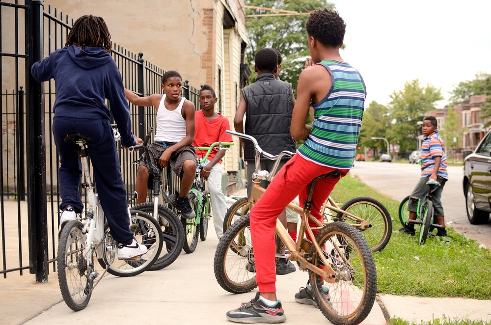 Image: Photo of six Black boys sitting on their bikes. Three boys have their backs toward the camera while three are facing the camera but looking at each other. Photo courtesy of the artist.