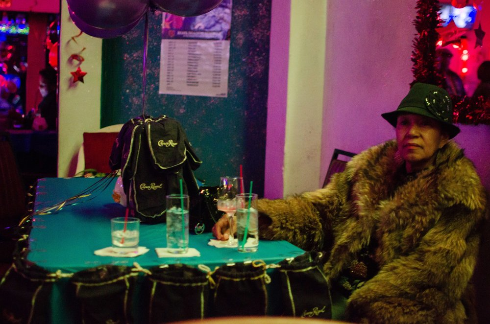 Image: An older Black woman sits at a table. She is wearing a brown fur coat and a black hat with a brooch on the side. She gazes past the camera with a slight smile on her face. On the teal table in front of her is a large black Crown Royal bag and glasses with clear liquid and straws in them. Photo courtesy of the artist.